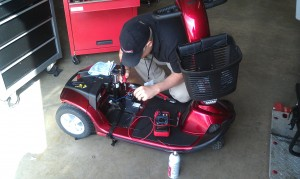 Male field technician working on a three-wheeled mobility scooter
